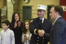 Chris Pratico shakes hands with First Selectman Peter Tesei as his wife, Toni Ann Anselmo, and twins, Michael and Sam, 12, applaud during his Fire Marshal promotion ceremony at the Public Safety Complex in Greenwich, Conn. Tuesday, Dec. 12, 2017. Fire Marshal Pratico was promoted from his previous rank of Deputy Fire Marshal. Deputy Chief Thomas Zack, Firefighter Theodore Ruehl and Marion Wood were also honored for their longtime service at the ceremony.