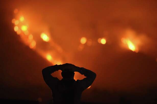 A man watches the Thomas Fire in the hills above Carpinteria, California, December 11, 2017. The Thomas Fire in California's Ventura and Santa Barbara counties has consumed more than 230,000 acres over the past week making it the fifth largest fire in the state's history. If the House Republican tax bill became law, victims of hurricanes in Texas and Florida who've yet to account for all their losses could deduct them on their 2018 taxes. Not so for victims of the California wildfires.
