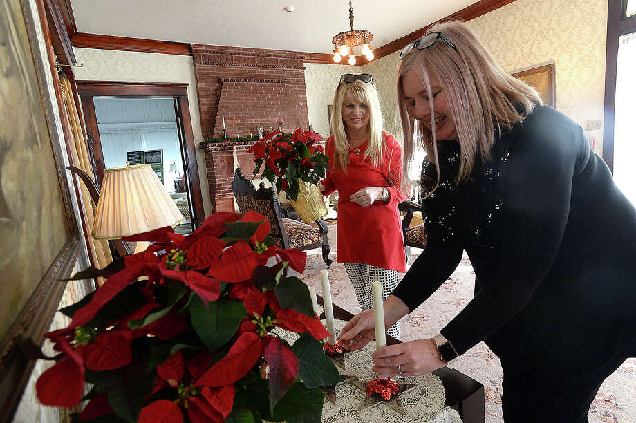 Beaumont Heritage Society members, including Alicia McKibbin (left) and Chevelle Thomas joke with one another as they set out poinsettia plants and check the batteries on candles at the Chambers House as they put the finishing touches on the holiday decor for their Vintage Christmas event this Thursday. From 6 - 8 p.m. visitors can tour the home, which is decorated with the family's orginal ornaments, cards, and other holiday items. The Sweet Adelines will perform Christmas carols to add to the holiday festivities.  The McFaddin - Ward House will have an event that evening, as well, opening its doors from 5 - 7 p.m. for an Eggnog Open House. Photo taken Tuesday, December 12, 2017 Kim Brent/The Enterprise Photo: Kim Brent / BEN