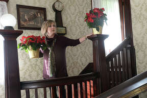 Beaumont Heritage Society members, including Janci Kimball, set out poinsettia plants at the Chambers House as they put the finishing touches on the holiday decor for their Vintage Christmas event this Thursday. From 6 - 8 p.m. visitors can tour the home, which is decorated with the family's orginal ornaments, cards, and other holiday items. The Sweet Adelines will perform Christmas carols to add to the holiday festivities.  The McFaddin - Ward House will have an event that evening, as well, opening its doors from 5 - 7 p.m. for an Eggnog Open House. Photo taken Tuesday, December 12, 2017 Kim Brent/The Enterprise