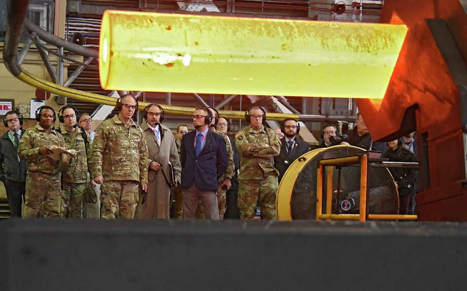 Gustave (Gus) Perna, fifth from left, a United States Army four-star general who serves as Commander of the United States Army Materiel Command, watches as a gun barrel is transported after being taken out of a furnace in the rotary forge building as he visits the Watervliet Arsenal on Monday, Dec. 11, 2017 in Watervliet, N.Y. (Lori Van Buren / Times Union) Photo: Lori Van Buren / 20042358A