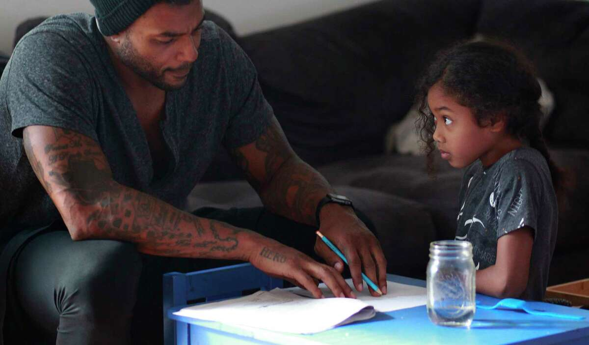 Larry Johnson helps his 7-year-old daughter, Jaylen, with homework in his Fort Lauderdale, Florida, residence. Their relationship is the only thing capable of pulling Johnson back from the edge, he says. Must credit: Photo by Andrew Innerarity for The Washington Post