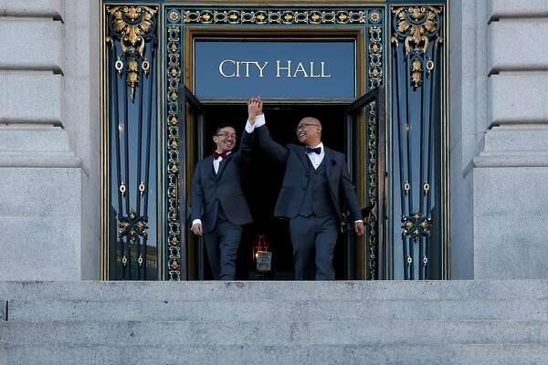 Derrick and Orlando Macaranas have wedding photos taken behind a growing memorial after exchanging their vows at City Hall on the day Mayor Ed Lee died in San Francisco, Calif. on Tuesday, Dec. 12, 2017.