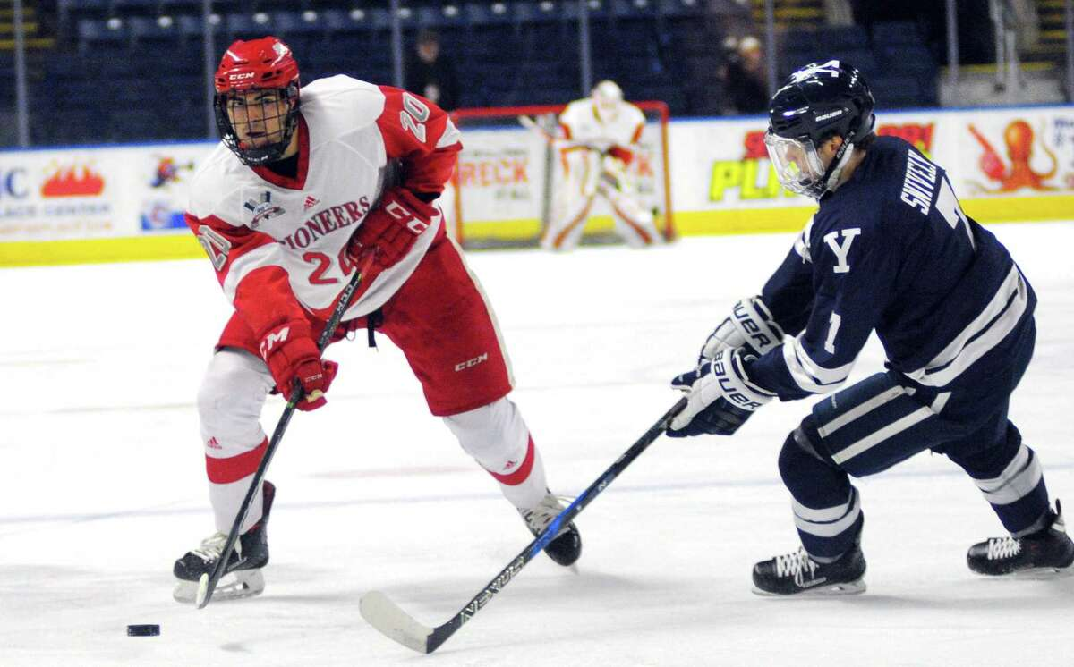 Sacred Heart's Vito Bavaro passes the puck as Yale's Joe Snively, right, looks to intercept during college hockey action at the Webster Bank Arena in Bridgeport, Conn., on Saturday Dec. 9, 2017.