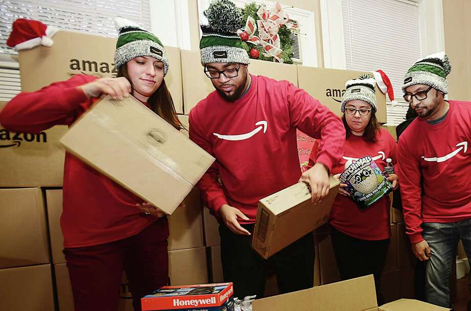 Meagan Maloney, a seasonal process assistant, left, and Christopher Thompson, a process assistant, employees from Amazon's sortation center in Wallingford, unbox items at Junta for Progressive Action in New Haven Tuesday during the Amazon Holiday Giving Tour. Photo: Catherine Avalone / Hearst Connecticut Media / New Haven Register