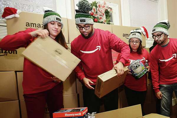 Meagan Maloney, a seasonal process assistant, left, and Christopher Thompson, a process assistant, employees from Amazon's sortation center in Wallingford, unbox items at Junta for Progressive Action in New Haven Tuesday during the Amazon Holiday Giving Tour.