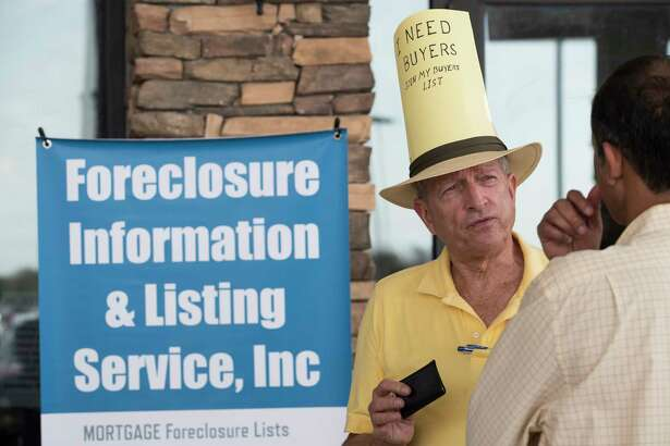 Mike Rutherford talks to a potential customer during a foreclosed property auction at the Bayou City Event Center on Tuesday, Dec. 5, 2017, in Houston. ( Brett Coomer / Houston Chronicle )