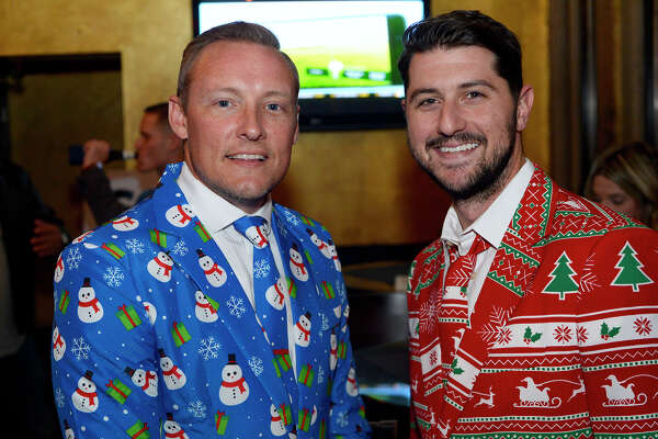 Jason Wagner and John Arcana during the Southeast Texas Young Professionals Organization mixer at The Grill on Tuesday night. The group collected Christmas gifts for teenagers under Child Protective Services care.  Photo taken Tuesday 12/12/17 Ryan Pelham/The Enterprise