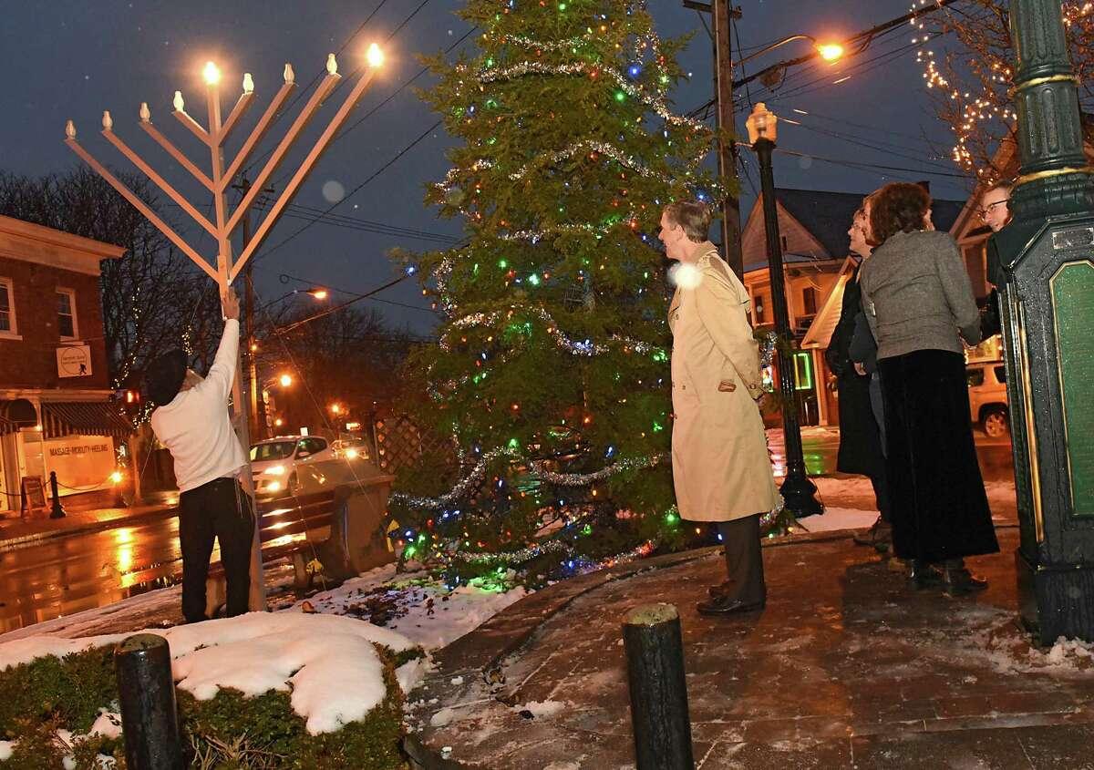 Rabbi Nachman Simon, left, lights a giant Menorah in a Hanukkah Menorah lighting at the Four Corners on Tuesday, Dec. 12, 2017, in Delmar, N.Y. (Lori Van Buren / Times Union)