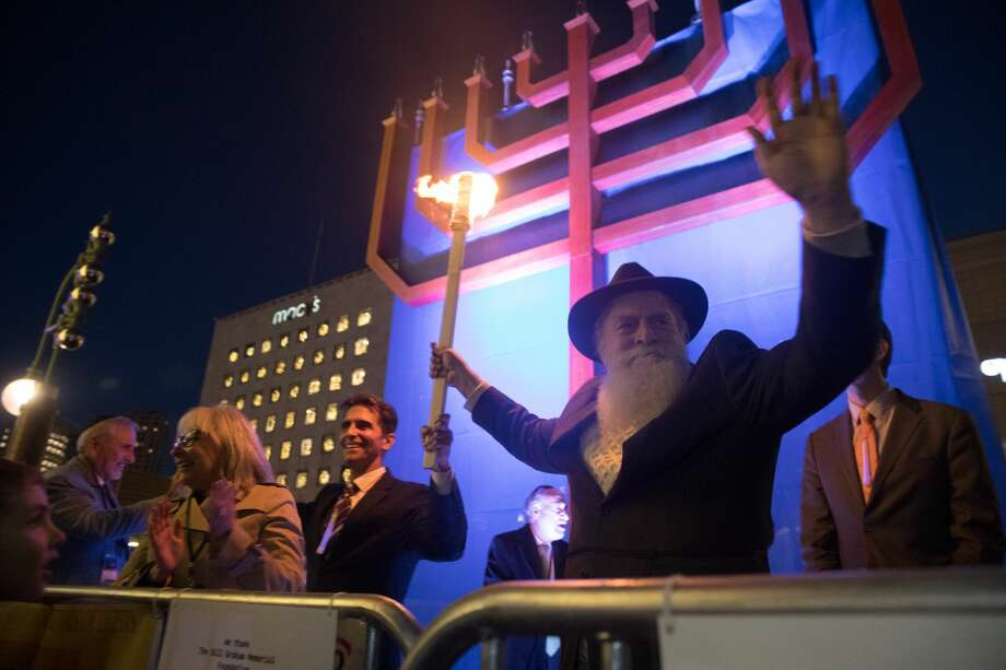 Chabad SF Rabbi Yosef Langer and Mark Leno hold a torch before lighting the Bill Graham menorah in San Francisco's Union Square on the first night of Hanukkah Tuesday evening December 12, 2017. Photo: Douglas Zimmerman / SFGate