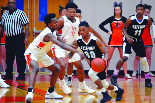 Edwardsville's Jaylon Tuggle, left, defends with teammate R.J. Wilson, behind, providing support against Gateway on Tuesday.