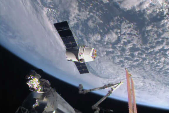 The SpaceX Dragon 6 resupply capsule nears the International Space Station in 2015. Elon Musk's company expects to send paying tourists around the moon next year.