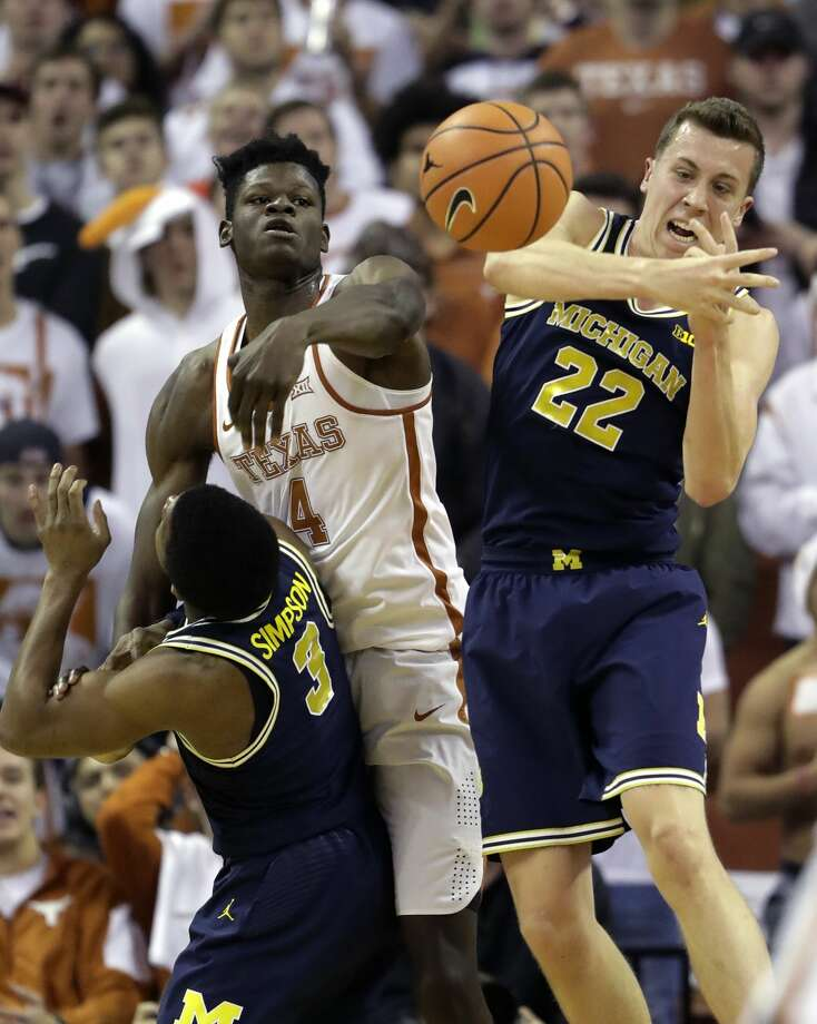 Texas forward Mohamed Bamba (4) battles Michigan guard Duncan Robinson (22) and guard Zavier Simpson (3) for a rebound during the first half of an NCAA college basketball game, Tuesday, Dec. 12, 2017, in Austin, Texas. (AP Photo/Eric Gay) Photo: Eric Gay/Associated Press