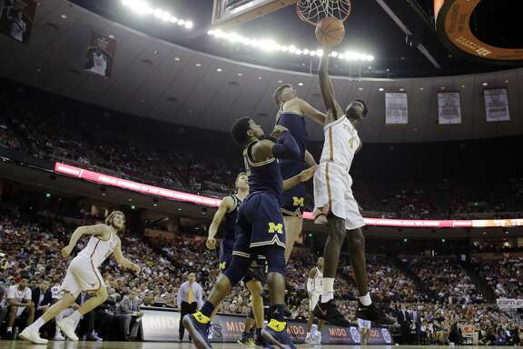 Texas forward Mohamed Bamba (4) scored over Michigan defenders Jon Teske (15) and Zavier Simpson (3) during the second half of an NCAA college basketball game, Tuesday, Dec. 12, 2017, in Austin, Texas. Michigan won 59-52. (AP Photo/Eric Gay)