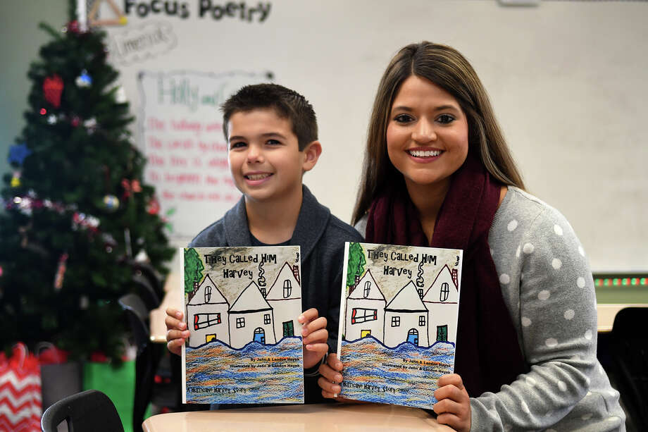 "Landon Hayek, 9, left, a fourth-grader at Creekview Elementary School, and his teacher, Kristin Khoobiar, show off copies of ""They Called Him Harvey"", a book about Hurricane Harvey that he co-authored and illustrated with his mom Jennifer. (Photo by Jerry Baker/Freelance) Photo: Jerry Baker, Freelance / Freelance"