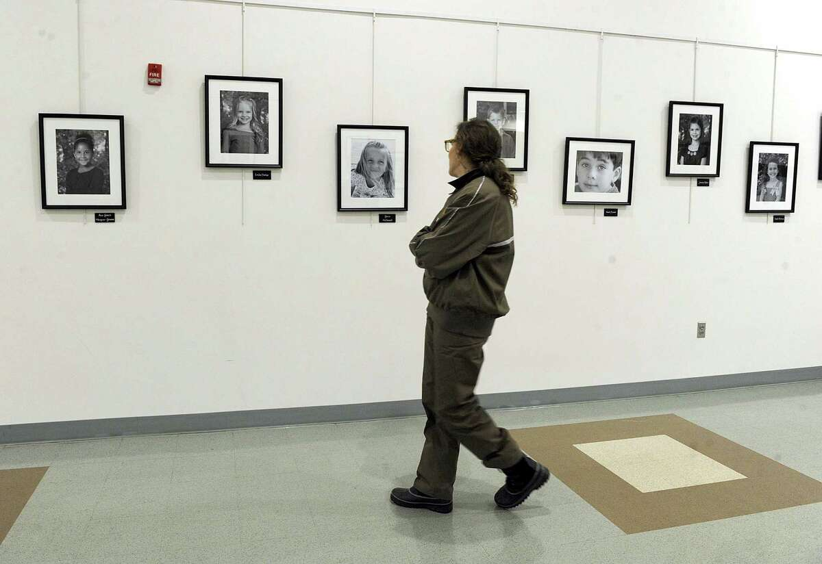 A passerby looks at the gallery of portraits of victims of the Sandy Hook School shooting that hang in hallway of the Newtown Municipal Center, Tuesday, Dec. 12, 2017.