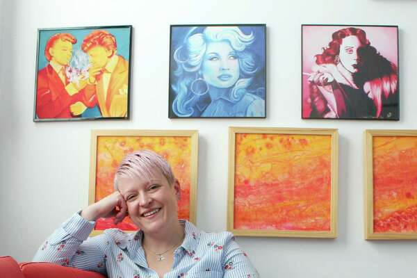 Niki Key at her studio inside at 80 Old Ridgefield Road, with prints of her three paintings currently exhibited at Wilton Library.