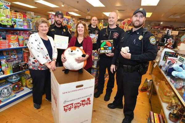 """Employees from The Toy Chest with Wilton police Officer Eric Patenaude,Wilton firefighters Don Scarpetti and Mike Pryor and Wilton police Officer Shawn Frendt at Wilton's """"Stuff-a-Cruiser"""" event in December 2015."""