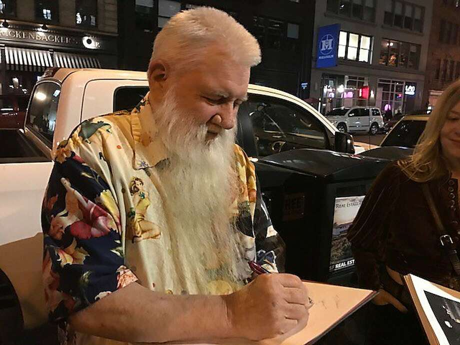 Last Gasp publisher Ron Turner signs books outside the party. Photo: Leah Garchik, San Francisco Chronicle