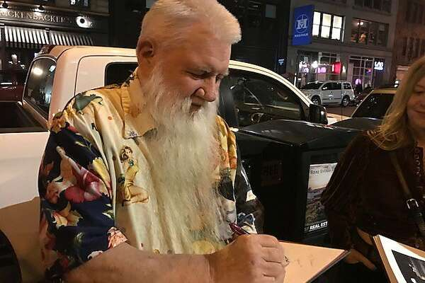 Last Gasp publisher Ron Turner signs books outside party for 'Who Killed Hunter S. Thompson?'