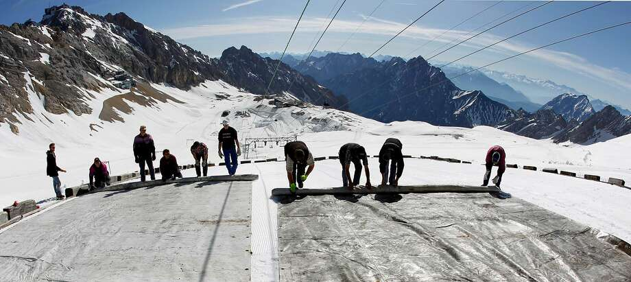 Workers on the peak of Germany's highest mountain, Zugspitze, in the southern part of the country, cover the glacier with oversize plastic sheeting in May 2011. It's meant to keep the glacier from melting during the summer — part of the fight against climate change. Photo: Matthias Schrader, Associated Press