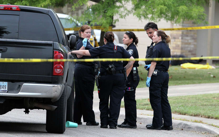 San Antonio police and investigators work at the scene of a fatal shooting that took place around 3:00 a.m. Friday July 27, 2012 on the 2000 block of Field Wood on the city's West Side. An under cover police officer shot the man who was the ex-boyfriend of a woman who called the officer asking for help. The woman was shot in the torso and wrist and the police officer was not injured. Photo: JOHN DAVENPORT, San Antonio Express-News / SAN ANTONIO EXPRESS-NEWS