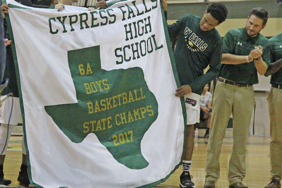 Cypress Falls High School senior Nigel Hawkins (second from right) and basketball assistant coach Mick Hoffman look at the Golden Eagles' banner commemorating the team's 2016-2017 Class 6A state championship, which was revealed Nov. 28.