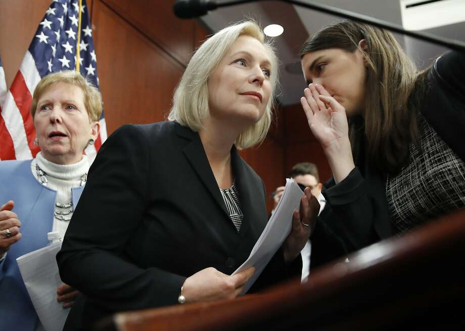 "Sen. Kirsten Gillibrand, D-N.Y., center, listens to a staffer before answering questions at a news conference, Tuesday, Dec. 12, 2017, on Capitol Hill in Washington. Gillibrand says President Donald Trump's latest tweet about her was a ""sexist smear"" aimed at silencing her voice.  Photo: Jacquelyn Martin, Associated Press"