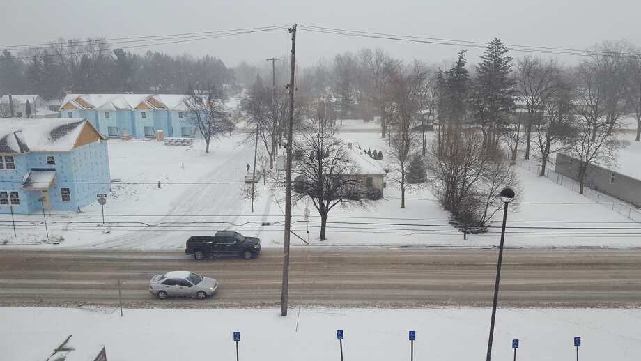 Motorists travel in downtown Midland during Wednesday's snowy weather.