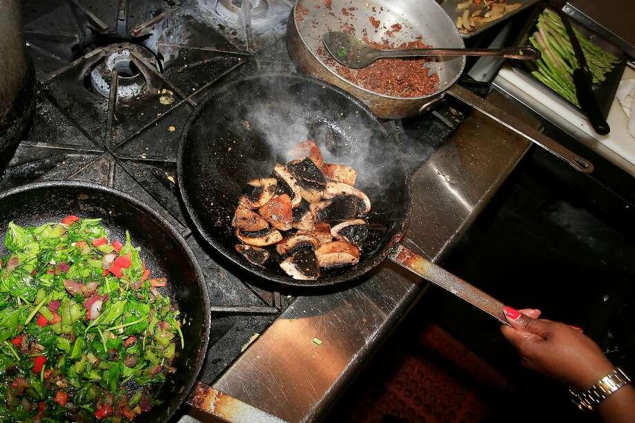 Chef Tamearra Dyson sautes portobello mushrooms and other ingredients for her vegan Wellington. Photo: Lea Suzuki, The Chronicle