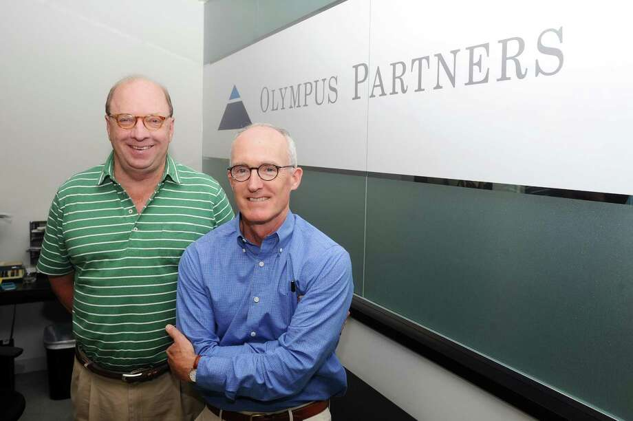 Olympus Partners managing partners Jim Conroy, center, and Rob Morris pose for a photo inside the private equity firm's offices in the Metro Center complex in downtown Stamford, Conn., on Wednesday, Sept. 20, 2017. Photo: Michael Cummo / Hearst Connecticut Media / Stamford Advocate