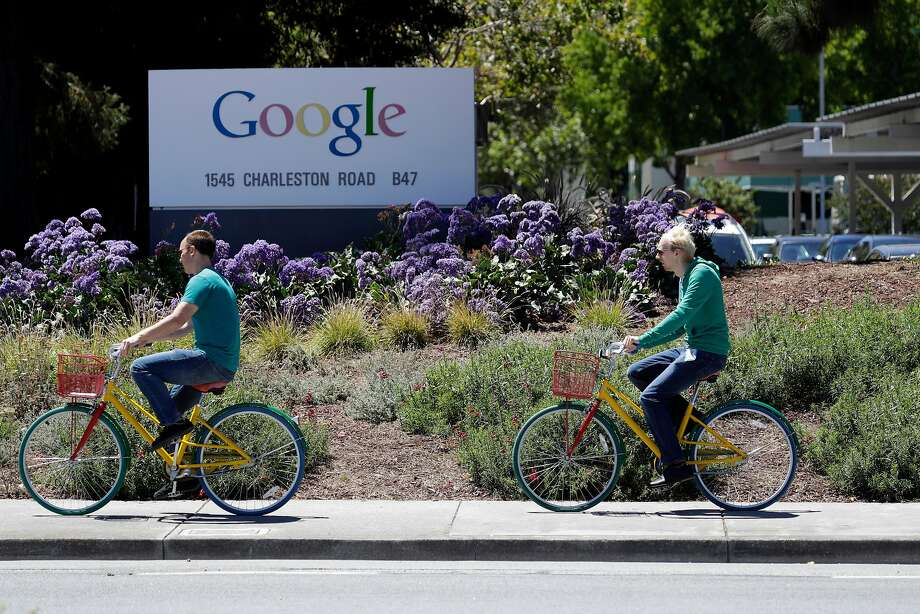 Cyclists ride past a Google sign at the company's headquarters. Google will be able to build housing in the North Bayshore area, where it is also planning a new campus, following the Mountain View City Council's approval of a plan to expand housing in the neighborhood by nearly 10,000 units. Photo: Marcio Jose Sanchez, Associated Press