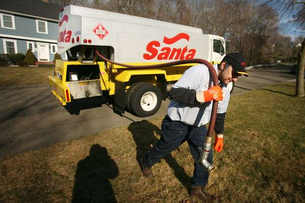 Jim Bender delivers oil from Santa Energy's four-wheel-drive delivery truck to a residence in Monroe.