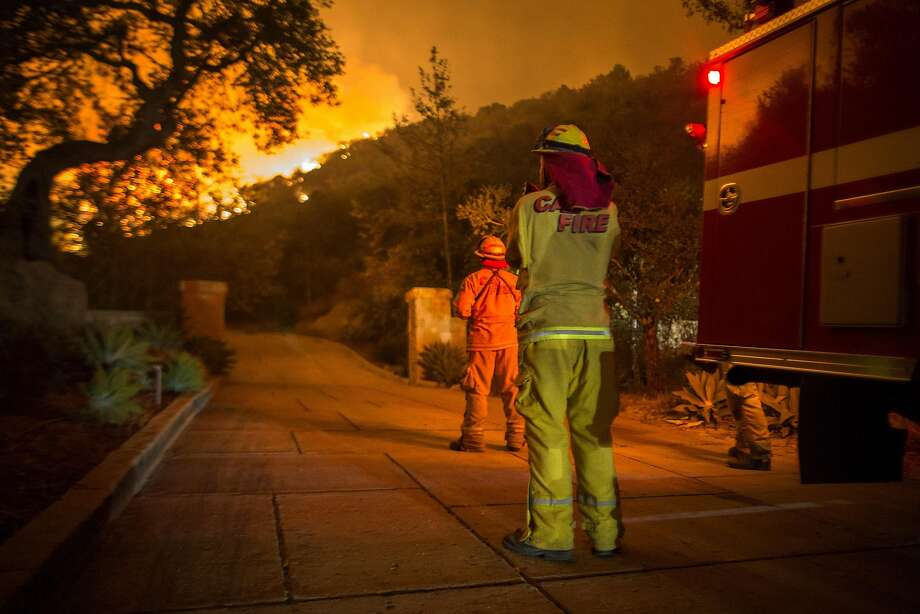 MONTECITO, CA - DECEMBER 12:  Firefighters watch flames as the Thomas Fire approaches homes on December 12, 2017 in Montecito, California. The Thomas Fire has spread across 365 miles so far and destroyed about 800 structures since it began on December 5 in Ojai, California.  (Photo by David McNew/Getty Images) Photo: David McNew, Getty Images