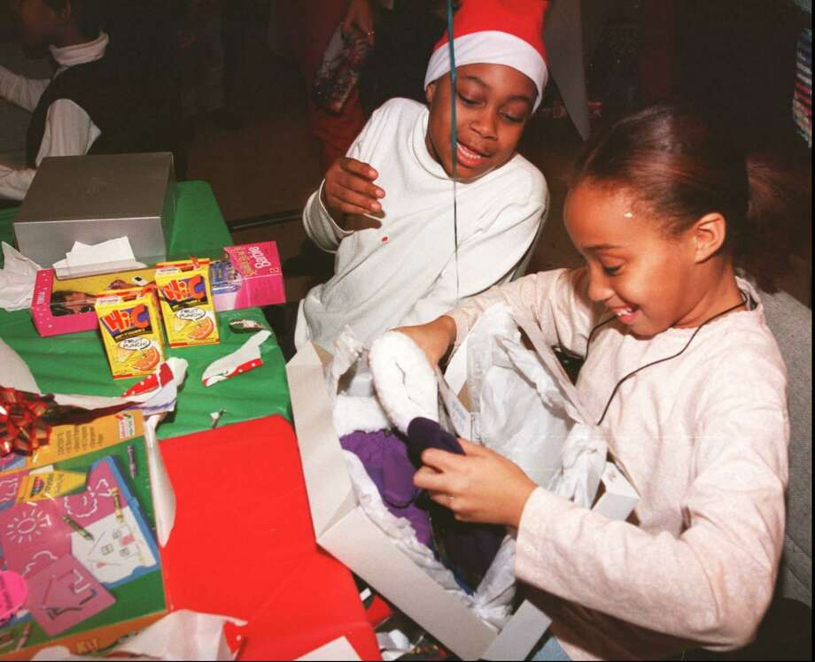 Adreana Andrews and Deanna Reason open gifts during a Christmas party at St. John's Episcopal Church on Dec. 18, 1996. Photo: Tom Ryan / File Photo