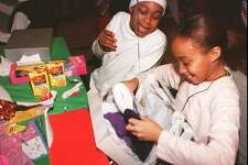 Adreana Andrews and Deanna Reason open gifts during a Christmas party at St. John's Episcopal Church on Dec. 18, 1996.