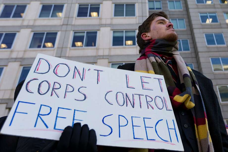 A man holds a 'Don't Let Corps Control Free Speech' protest sign during a demonstration against the repeal of net neutrality outside the Federal Communications Commission headquarters in Washington, DC on December 13, 2017. Photo: ALEX EDELMAN, AFP/Getty Images