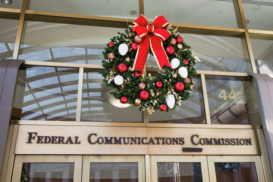 A holiday wreath hangs over the front entrance of the Federal Communications Commission headquarters building while a demonstration takes place across the street against the proposed repeal of net neutrality outside in Washington, DC on December 13, 2017. Photo: ALEX EDELMAN /AFP /Getty Images / AFP or licensors