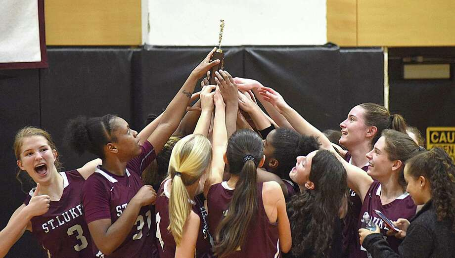 Members of the St. Luke's girls basketball team celebrate their 2017 FAA championship, which the Storm on Saturday with an 82-55 victory over Greenwich Academy at Carey Gymnasium in New Canaan. Photo: John Nash / Hearst Connecticut Media / Norwalk Hour