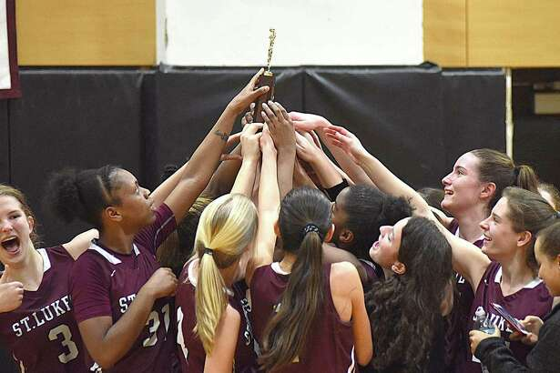Members of the St. Luke's girls basketball team celebrate their 2017 FAA championship, which the Storm on Saturday with an 82-55 victory over Greenwich Academy at Carey Gymnasium in New Canaan.
