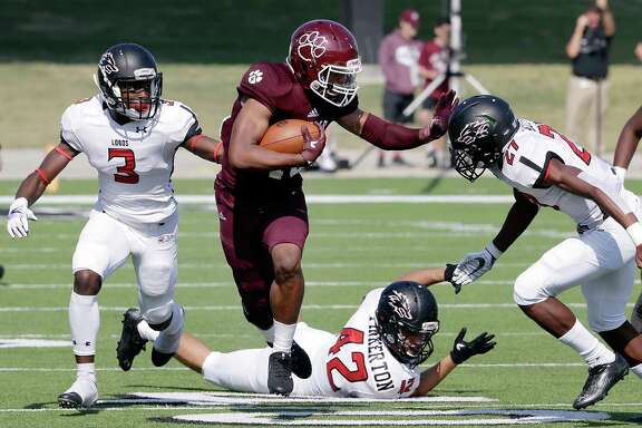 Cy-Fair's Trenton Kennedy (43) pushes through the hole between Langham Creek's Golden Eke (3), Brad Pinkerton and Corien Azema during the first half of their game Saturday, Nov. 11, 2017, in Houston, TX. (Michael Wyke / For the  Chronicle)