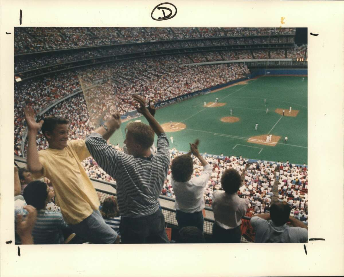 Scott Robinson, left, and Chuck Newton share a high five after an Astros hit in the first inning of Friday's game agains the Los Angeles Dodgers at the Houston Astrodome. The Astros scored four runs in that inning as they defeated Los Angeles and its ace pitcher, Orel Hershiser, 6-4. The win in the first game of a four-game series moved Houston within 2-1/2 games of the first place in the National League West. The official attendance at the game was 43,426, the largest crowd of the 1988 season.