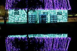 A building wrapped in lights is reflected in pond at Dewberry Farm,  7705 Farm to Market 362, shown Sunday, Dec. 10, 2017, in Brookshire. In addition to the Trail of Lights the buildings around the property are wrapped in lights. ( Melissa Phillip / Houston Chronicle )