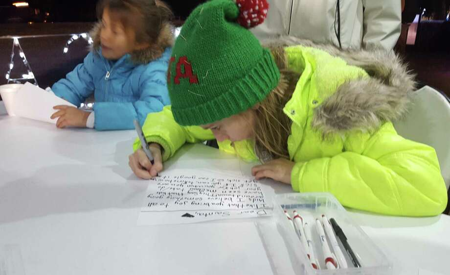 "Riley Speed, 9, of Universal City, takes her time making sure she spells everything right in the ""Letter To Santa"" she crafted Dec. 5 during Universal City's annual tree lighting ceremony Dec. 5 at City Hall. Photo: Jeff B. Flinn / NE Herald /Jeff B. Flinn / NE Herald"