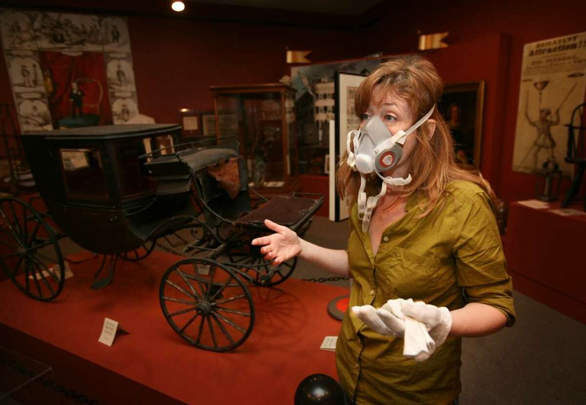 Barnum Museum Director Kathy Maher wears a respirator as she discusses the damage to the museum's collection that occured when windows were blown out during last Thursday's violent storm.