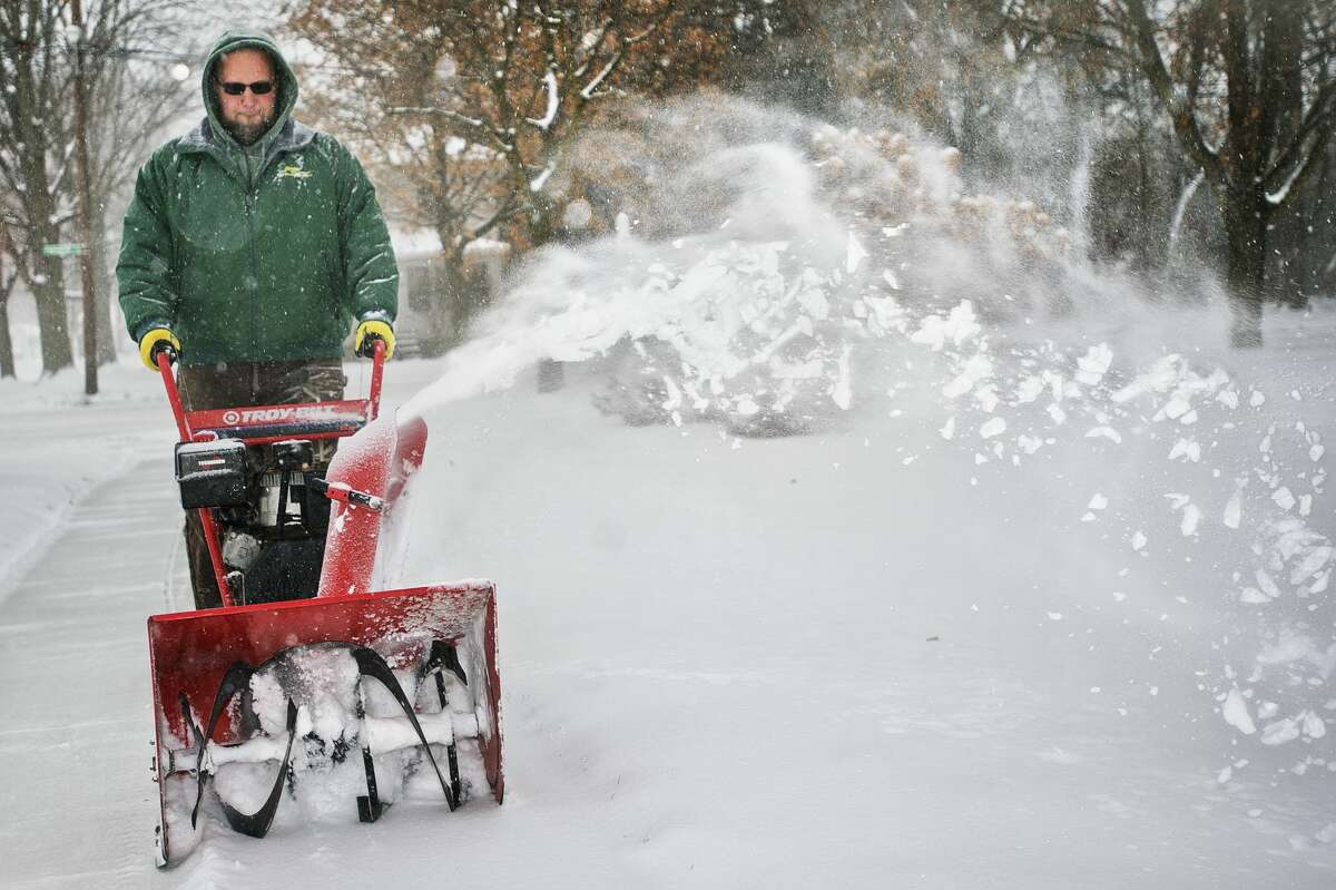 Adam Gohs with Randi's Green Thumb Service clears a sidewalk of snow at Memorial Presbyterian Church on Wednesday, Dec. 13, 2017. The National Weather Service issued a winter storm warning for Midland County, among other areas, until midnight on Wednesday. Up to 9 inches of snow is expected to accumulate. (Katy Kildee/kkildee@mdn.net)
