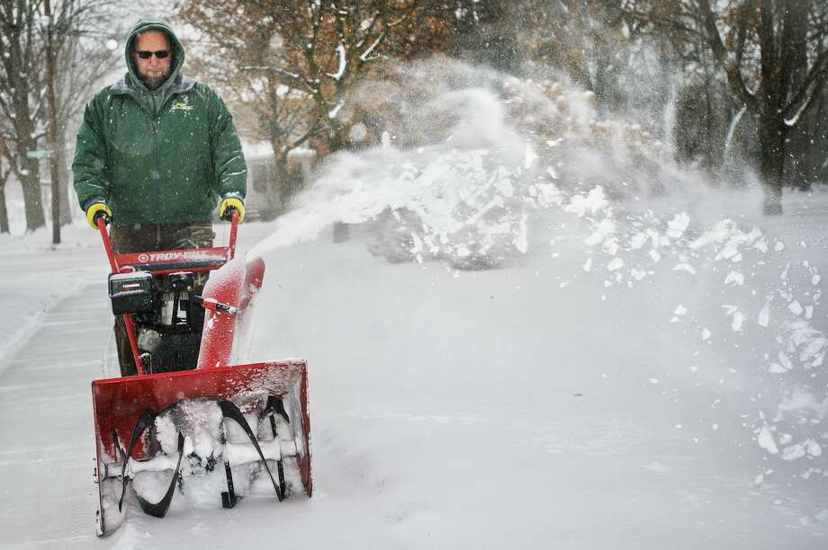 Adam Gohs with Randi's Green Thumb Service clears a sidewalk of snow at Memorial Presbyterian Church on Wednesday, Dec. 13, 2017. The National Weather Service issued a winter storm warning for Midland County, among other areas, until midnight on Wednesday. Up to 9 inches of snow is expected to accumulate. (Katy Kildee/kkildee@mdn.net) Photo: (Katy Kildee/kkildee@mdn.net)