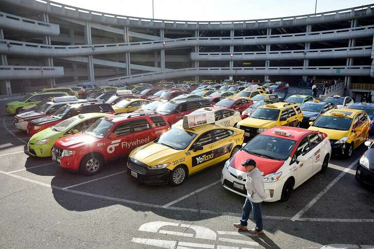 Lines of taxis sit in one of three waiting lots at San Francisco International Airport, where drivers can wait up to four hours for a fare, in San Francisco, Calif., on Wednesday December 13, 2017.