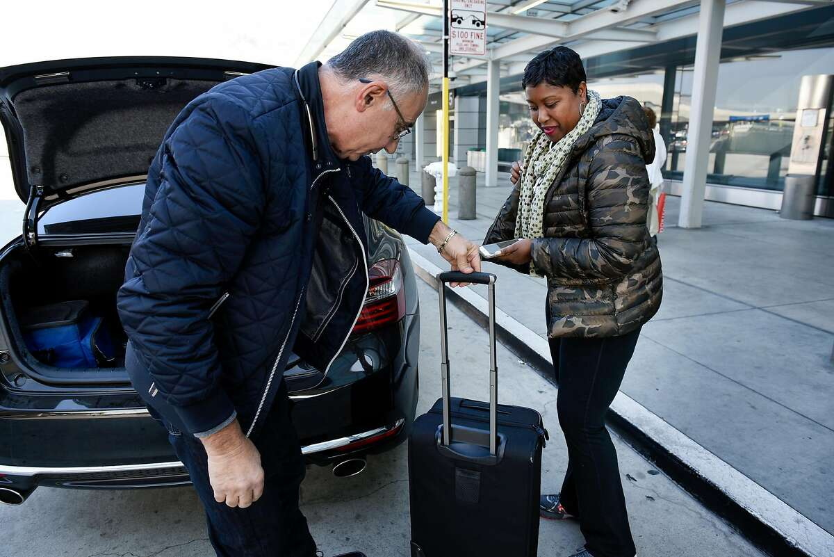 Lyft driver Ghassan Bon Zaid, left, helps passenger Monda Webb, arriving from Maryland, with her bags at San Francisco International Airport in San Francisco, Calif., on Wednesday December 13, 2017.