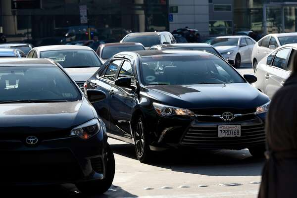 A car with Uber and Lyft tags is seen in the traffic in front of the arrivals terminal at San Francisco International Airport in San Francisco, Calif., on Wednesday December 13, 2017.